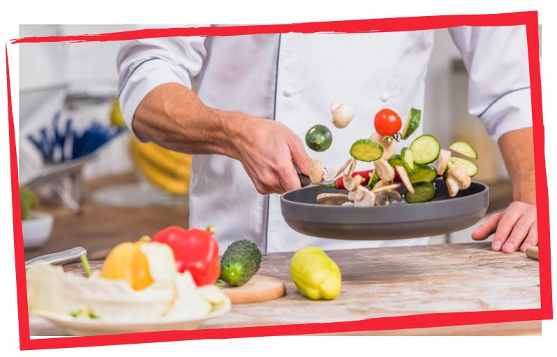 Cocinero haciendo frutas y verduras ecológicas